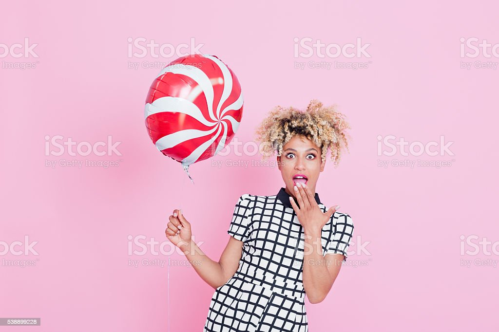Afro American young woman holding candy balloon Summer portrait of happy, energetic afro american young woman wearing grid check playsuit, standing against pink background, holding candy balloon. 2016 Stock Photo