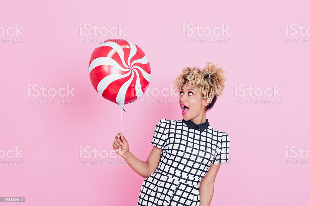 Afro American young woman holding candy balloon Summer portrait of happy, afro american young woman wearing grid check playsuit, standing against pink background, holding candy balloon. 2016 Stock Photo
