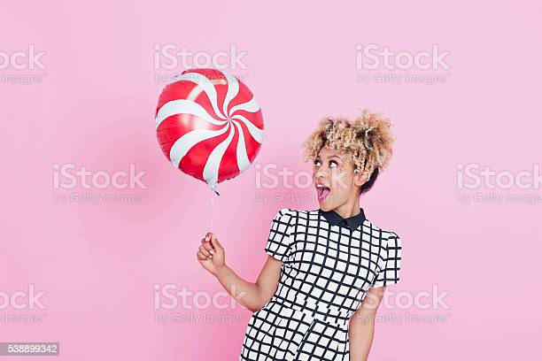Afro American Young Woman Holding Candy Balloon Stock Photo - Download Image Now