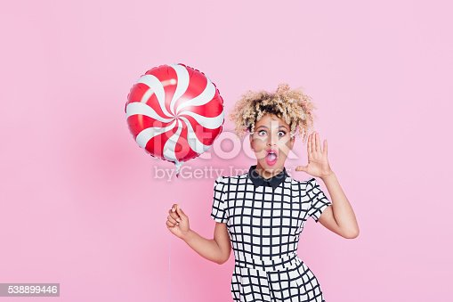 538883870istockphoto Afro American young woman holding candy balloon 538899446