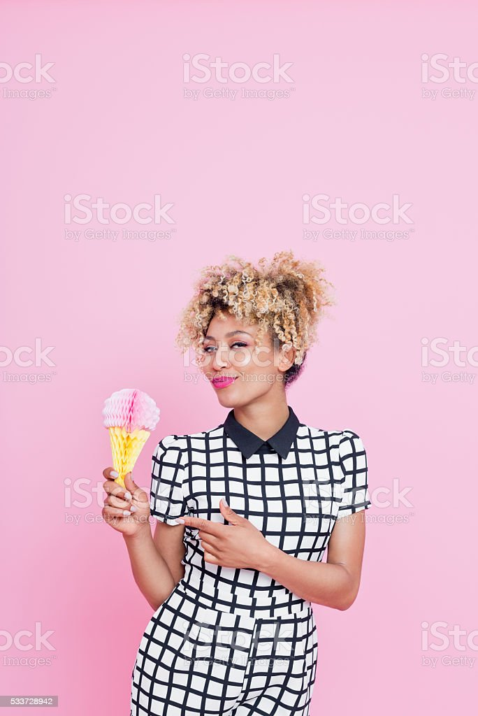 Afro American young woman holding ice cream honeycomb decorations Summer portrait of happy, afro american young woman wearing grid check playsuit, standing against pink background, holding ice cream honeycomb decorations and smiling. 25-29 Years Stock Photo