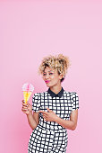 Summer portrait of happy, afro american young woman wearing grid check playsuit, standing against pink background, holding ice cream honeycomb decorations and smiling.