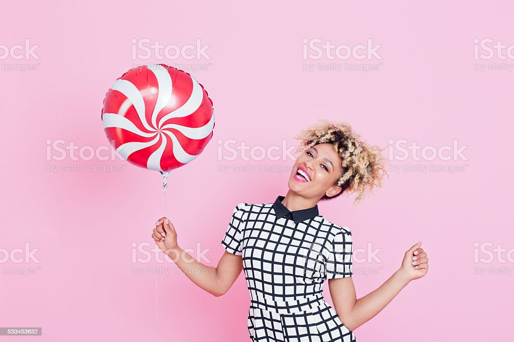 Afro American young woman holding lollypop balloon Summer portrait of happy, energetic afro american young woman wearing grid check playsuit, standing against pink background, holding lollypop balloon and laughing. 2016 Stock Photo