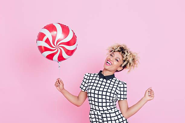 afro-american junge frau hält lollypop-ballon - frisuren 2016 frauen stock-fotos und bilder