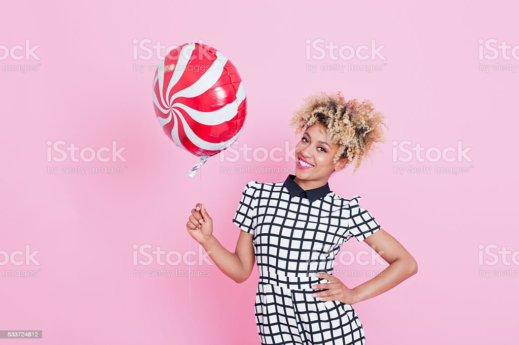 Afro American young woman holding lollypop balloon Summer portrait of happy, afro american young woman wearing grid check playsuit, standing against pink background, holding lollypop balloon and smiling. 2016 Stock Photo