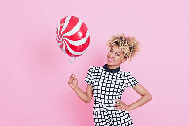 afro-american junge frau hält lollypop-ballon - modefarben sommer 2016 stock-fotos und bilder
