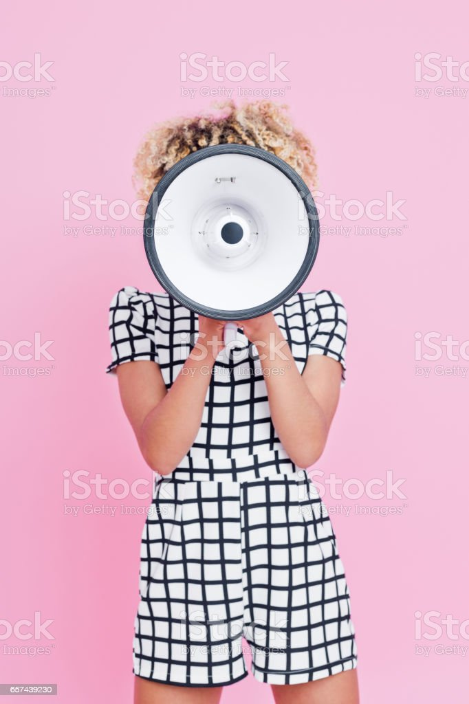 Afro american young woman holding megaphone Studio portrait of afro american young woman shouting into megaphone. Pink background. 20-24 Years Stock Photo
