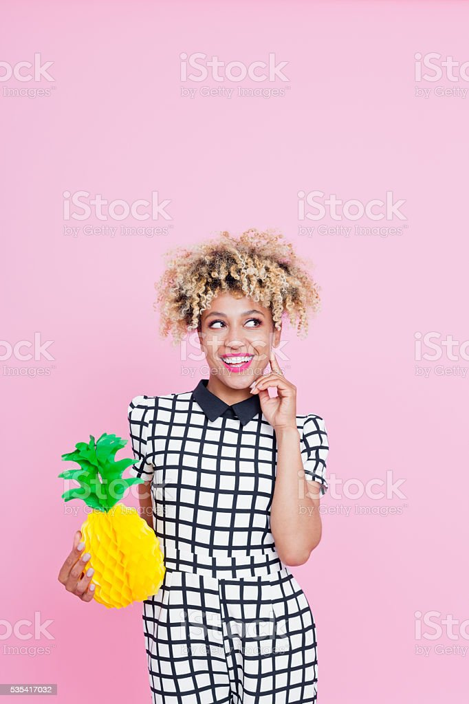 Afro American young woman holding pineapple honeycomb decorations Summer portrait of happy, afro american young woman wearing grid check playsuit, standing against pink background, holding pineapple honeycomb decorations looking up and smiling. 25-29 Years Stock Photo