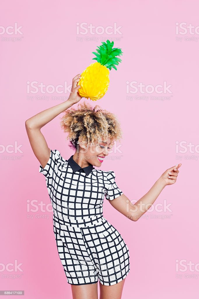 Afro American young woman holding pineapple honeycomb decorations Summer portrait of happy, afro american young woman wearing grid check playsuit, dancing against pink background, holding pineapple honeycomb decorations looking down and smiling. 25-29 Years Stock Photo