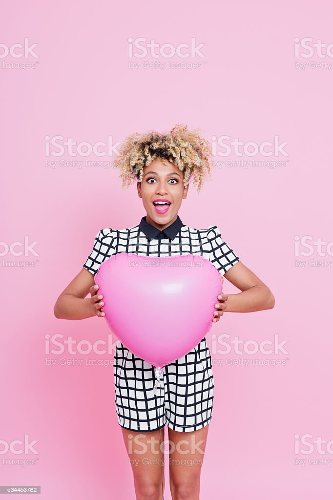 Afro American young woman holding pink heart shaped balloon Summer portrait of beautiful afro american young woman with surprised expression on her face. Wearing grid check playsuit, standing against pink background and holding Pink Heart Balloon. 2016 Stock Photo