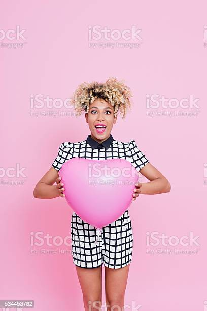 Afro American Young Woman Holding Pink Heart Shaped Balloon Stock Photo - Download Image Now