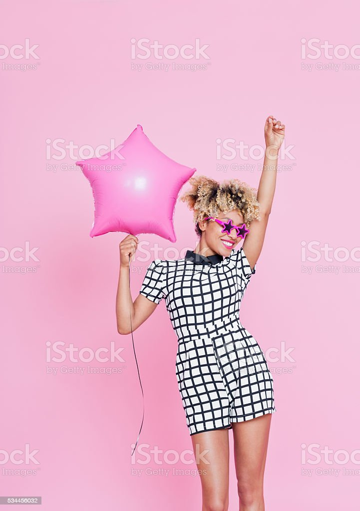 Afro American young woman holding Pink Star Foil Balloon Summer portrait of beautiful afro american young woman, wearing grid check playsuit, and star shaped sunglasses. She is standing against pink background with one hand raised and holding pink star balloon in another. Adult Stock Photo
