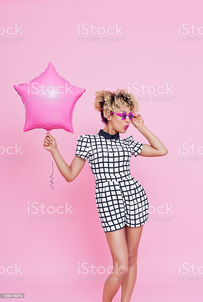 Afro American young woman holding Pink Star Foil Balloon Summer portrait of beautiful afro american young woman, wearing grid check playsuit, and star shaped sunglasses. Standing against pink background and holding pink star balloon in another. Adult Stock Photo