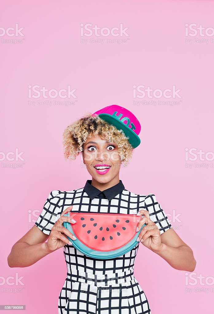 Afro American young woman holding watermelon bag Summer portrait of surprised, afro american young woman wearing grid check playsuit, standing against pink background, holding watermelon shaped bag. 20-29 Years Stock Photo