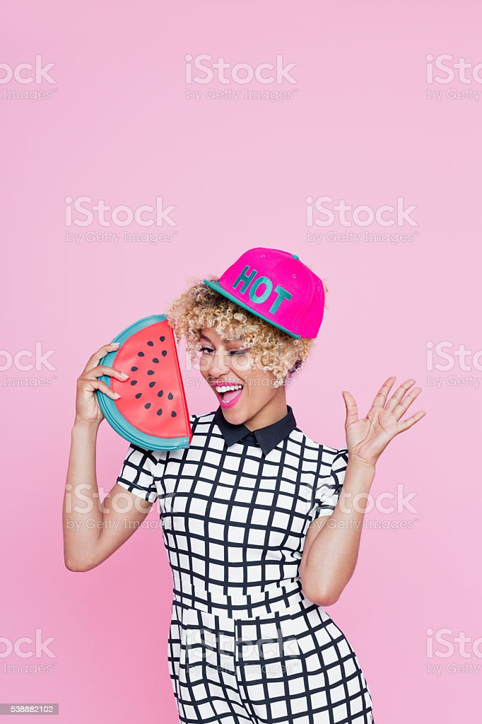 Afro American young woman holding watermelon bag Summer portrait of happy afro american young woman, wearing grid check playsuit, standing against pink background, holding watermelon shaped bag. 20-29 Years Stock Photo