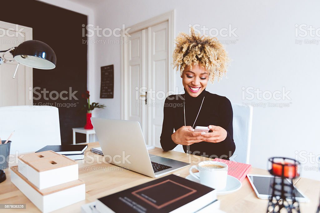 Afro american young woman in a home office Beautiful afro american young woman sitting at the desk in a home office and using a smart phone. Adult Stock Photo