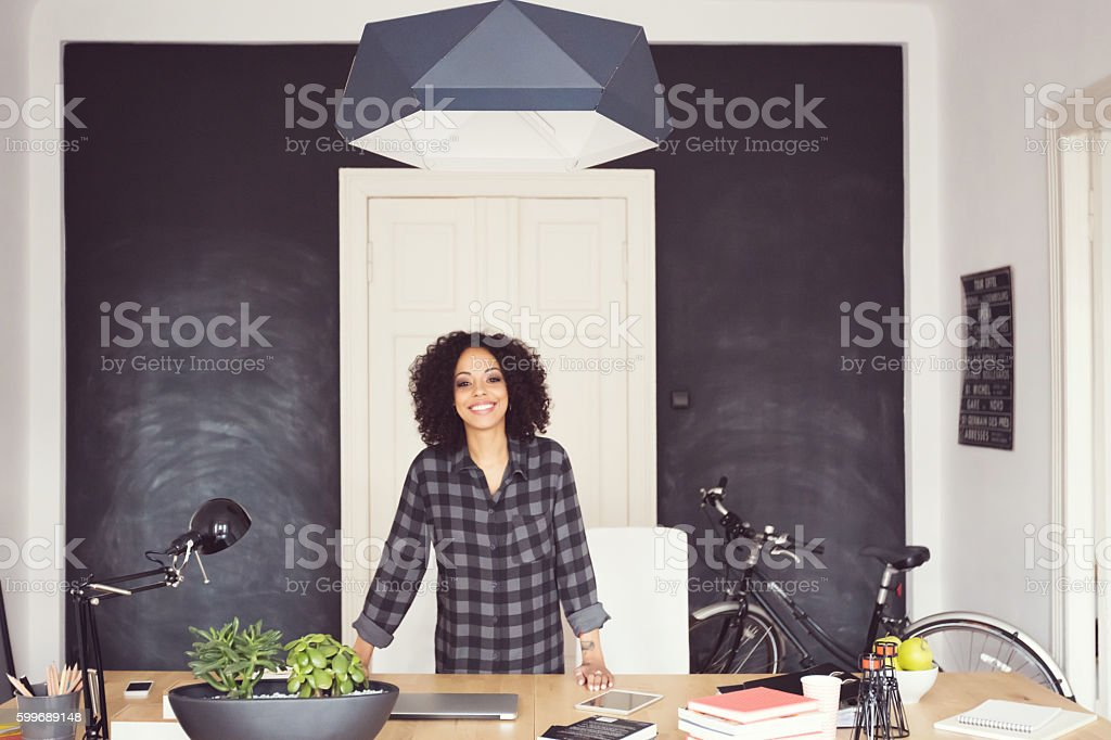 Afro american young woman in an office Afro american young woman in the office, smiling at camera. Wide angle view. Adult Stock Photo