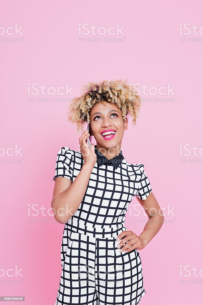 Afro American young woman on her moble Portrait of happy afro american woman talking on here mobile phone against pink background. She is wearing grid check playsuit. Studio shot. 25-29 Years Stock Photo