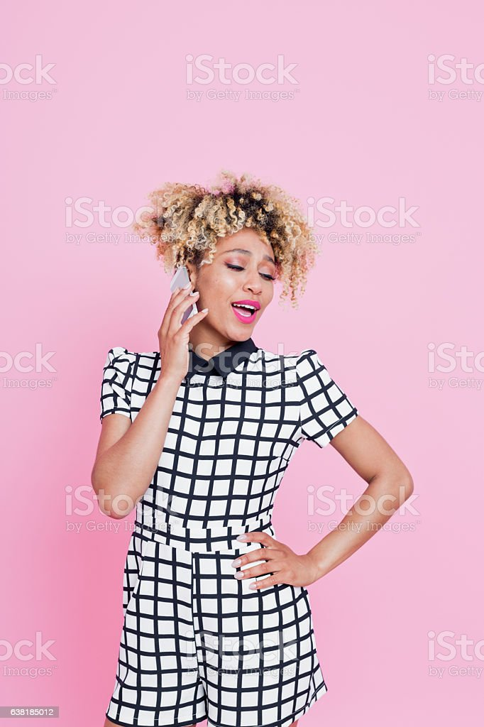 Afro American young woman on her moble Portrait of happy looking afro american woman talking on here mobile phone against pink background. She is wearing grid check playsuit. Studio shot. 25-29 Years Stock Photo