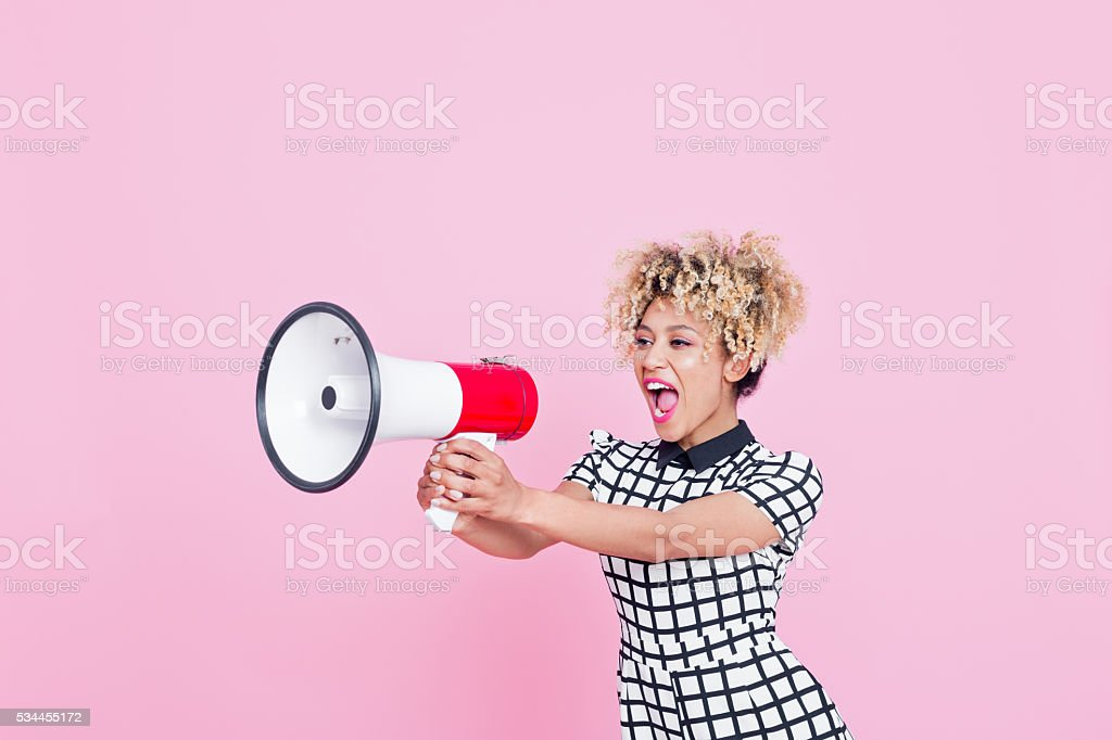 Afro American young woman shouting into megaphone Summer portrait of beautiful afro american young woman, wearing grid check playsuit, standing against pink background, shouting into megaphone. Studio shot. 20-29 Years Stock Photo