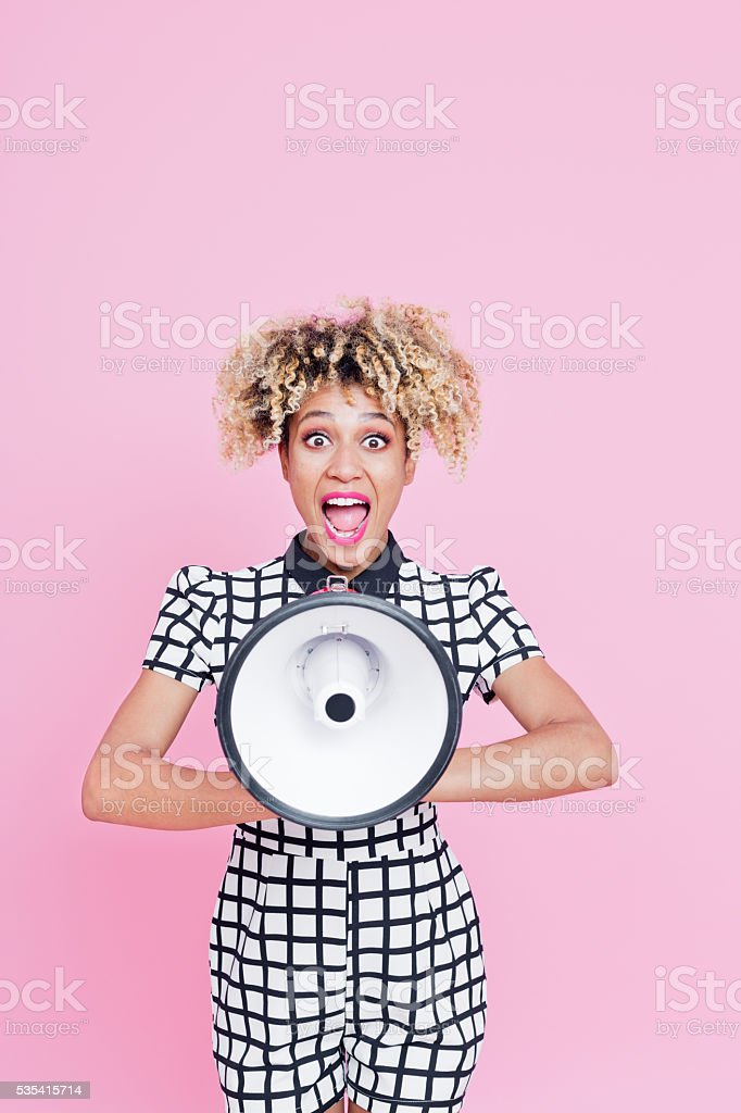Afro American young woman shouting into megaphone stock photo