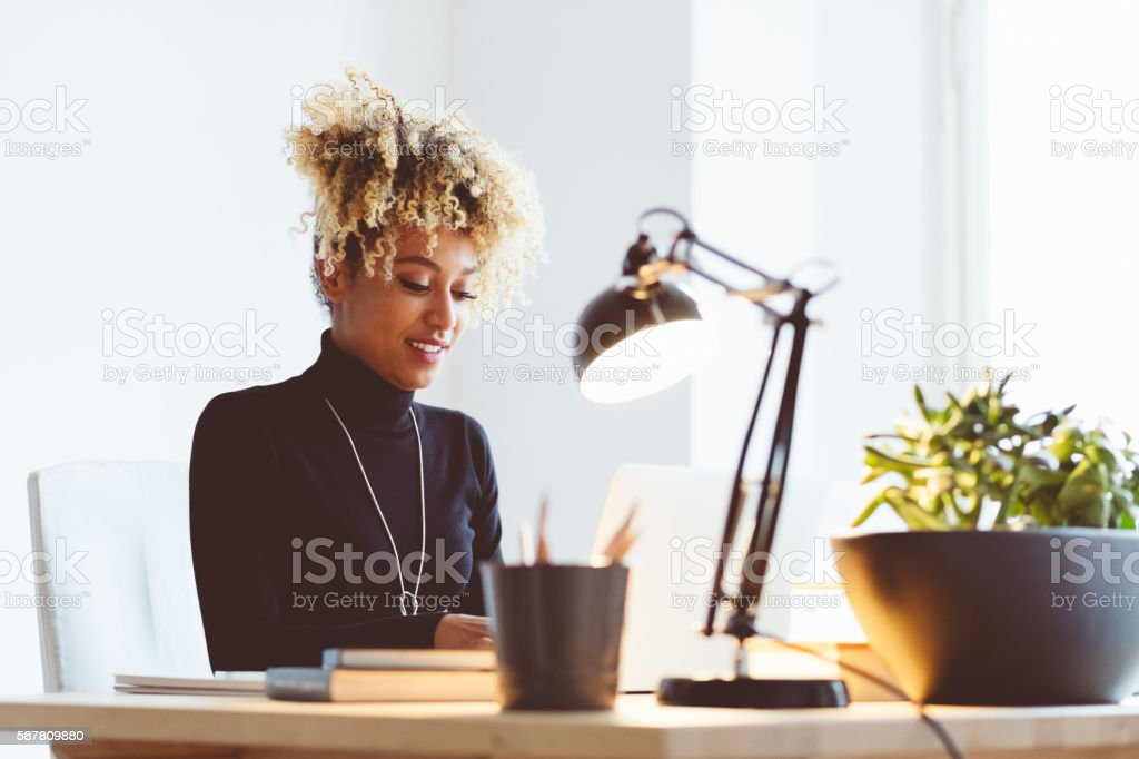 Afro american young woman using a laptop in an office Beautiful afro american elegant young woman sitting at the desk and using a laptop in an office or at home.  Adult Stock Photo