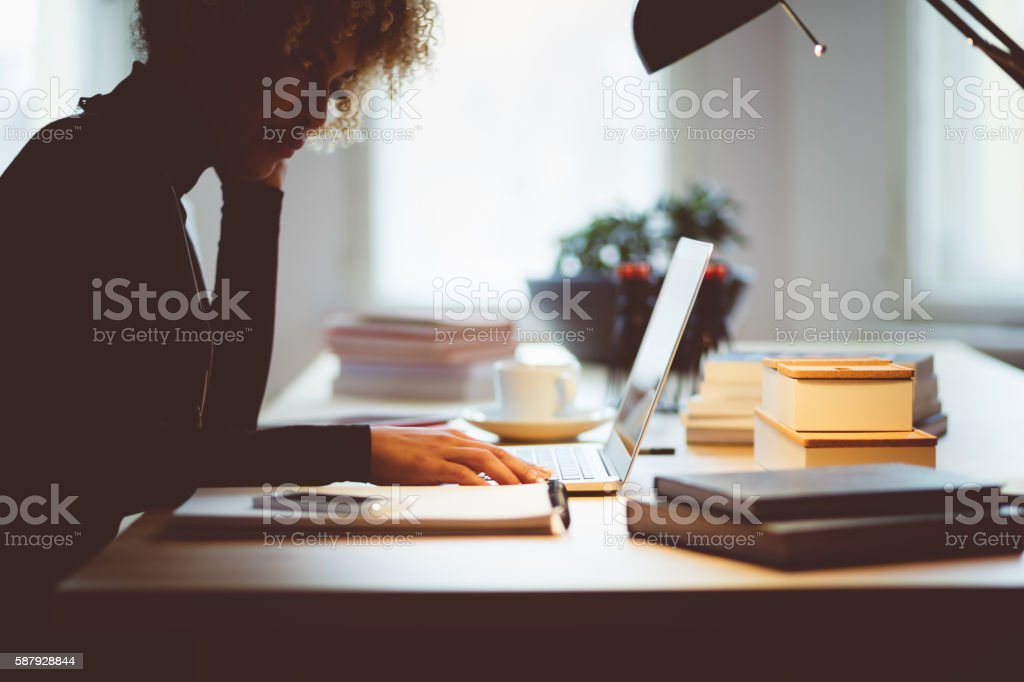 Afro american young woman using a laptop in an office Beautiful afro american elegant young woman sitting at the desk and using a laptop in an office or at home. Dark tone. Adult Stock Photo