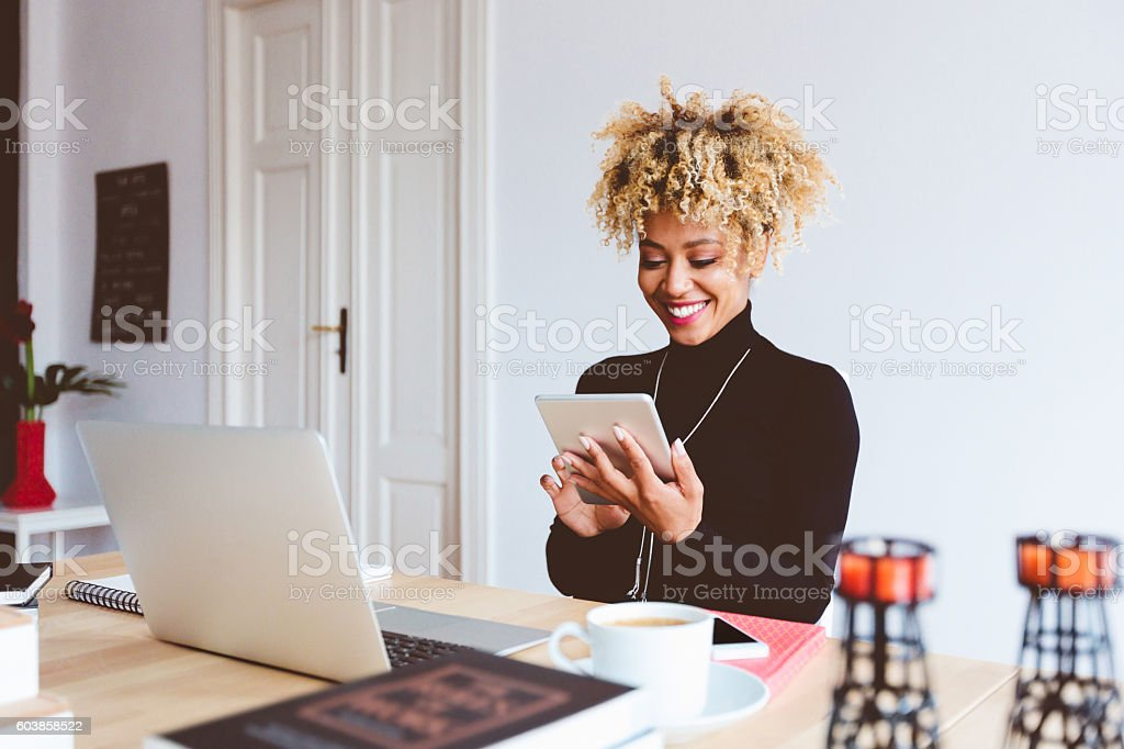 Afro american young woman using digital tablet in an office Beautiful afro american young woman using a digital tablet in an office, receiving good news, smiling. Adult Stock Photo