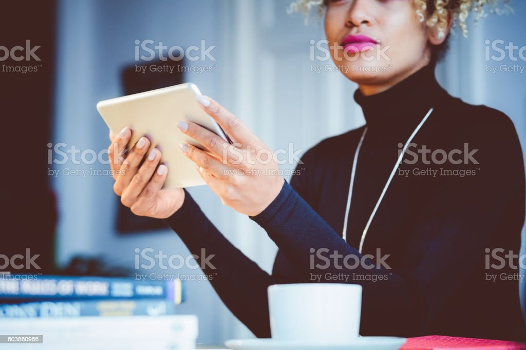 Afro american young woman using digital tablet in an office Beautiful afro american young woman using a digital tablet in an office. Focus on mobile device and hands. Adult Stock Photo