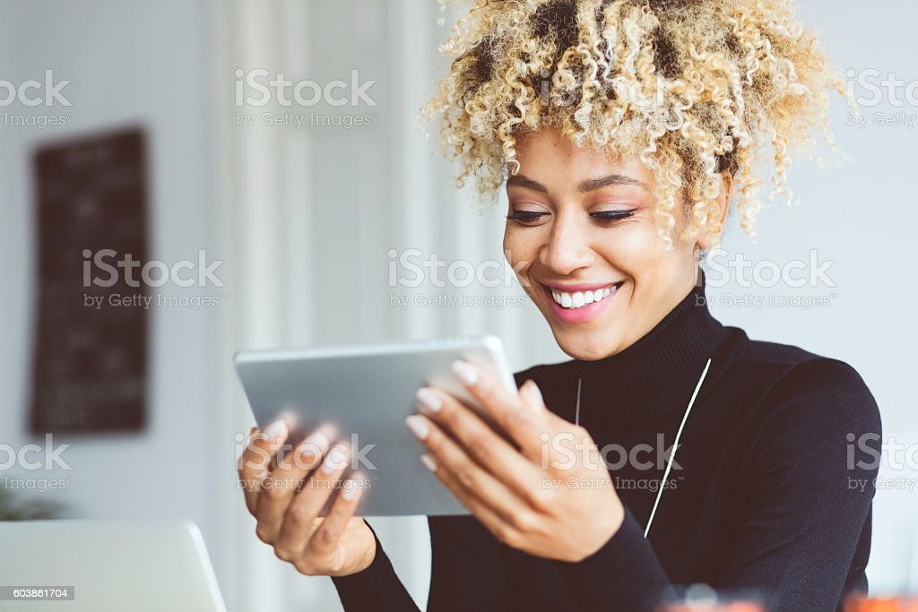 Afro american young woman using digital tablet in an office Beautiful afro american young woman using a digital tablet in an office, receiving good news, smiling. Close up of face. Adult Stock Photo