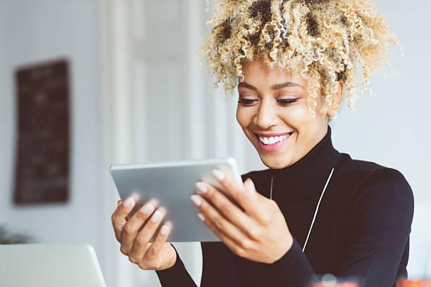 afro american young woman using digital tablet in an office - buona notizia foto e immagini stock