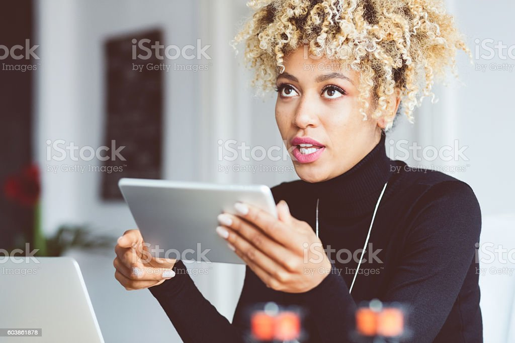 Afro american young woman using digital tablet in an office Beautiful afro american young woman using a digital tablet in an office. Adult Stock Photo