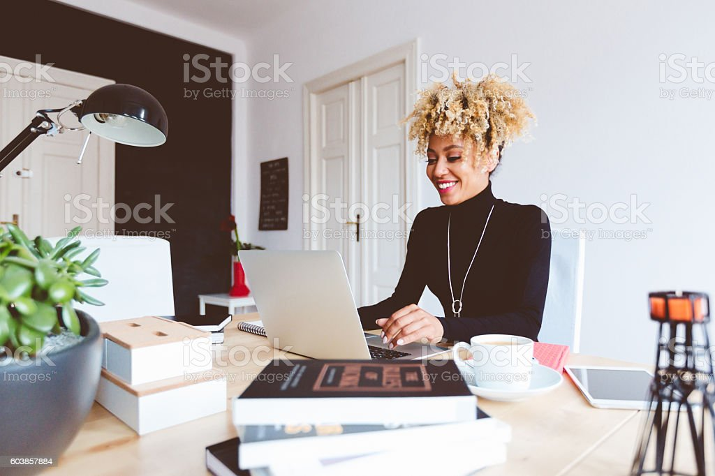 Afro american young woman using laptop in an office Beautiful afro american young woman sitting by the desk in a home office, using laptop. Adult Stock Photo