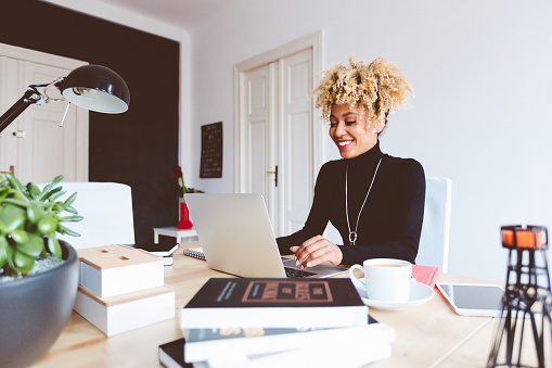 Afro American Young Woman Using Laptop In An Office Stock Photo - Download Image Now