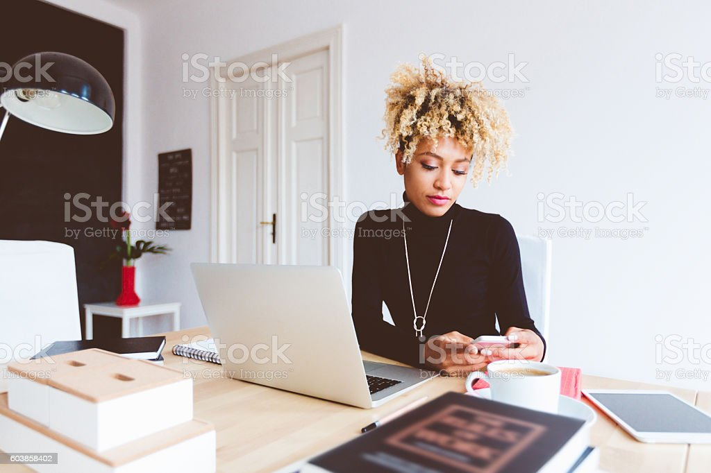 Afro american young woman using smart phone in an office Beautiful afro american young woman sitting by the desk and using a mobile phone in an office. Adult Stock Photo