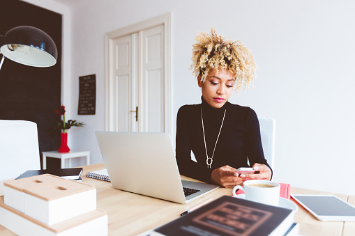 Afro American Young Woman Using Smart Phone In An Office Stock Photo - Download Image Now