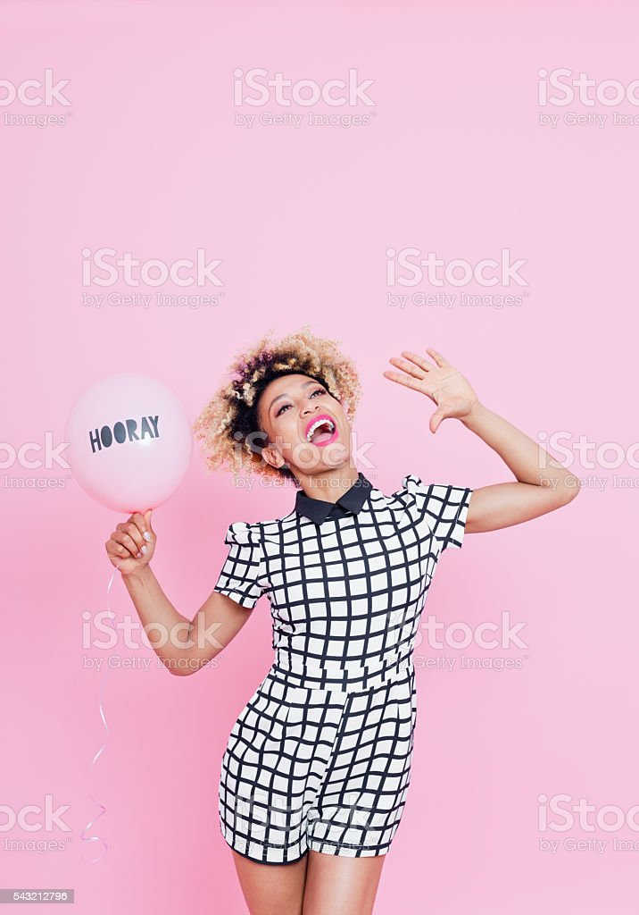 Afro American young woman with HOORAY balloon shouting Summer portrait of beautiful afro american young woman holding pink ballon with HOORAY copy, wearing grid check playsuit, standing against pink background and shouting. Studio shot. 20-29 Years Stock Photo