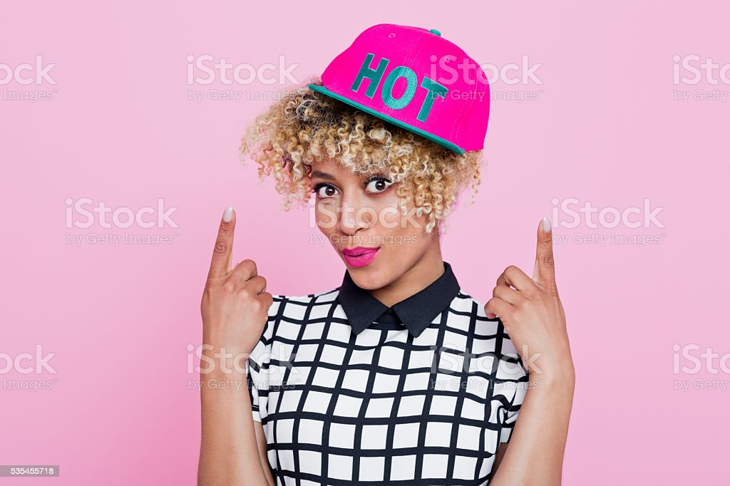 Afro American young woman with pink cap Summer portrait of happy, afro american young woman wearing grid check playsuit and pink baseball cap, standing with here fingers showing text HOT written at her cap, looking at camera and smiling. Studio shot, pink background. 20-29 Years Stock Photo