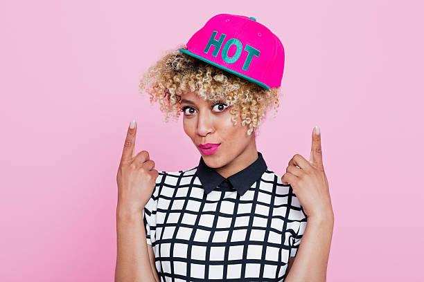 afro americana giovane donna con cappello rosa - capelli ossigenati foto e immagini stock