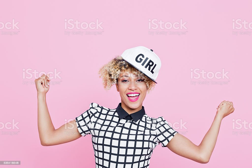 Afro American young woman with white cap Summer portrait of happy, afro american young woman wearing grid check playsuit and white baseball cap, standing with hands raised, looking at camera and smiling. Studio shot, pink background. 20-29 Years Stock Photo
