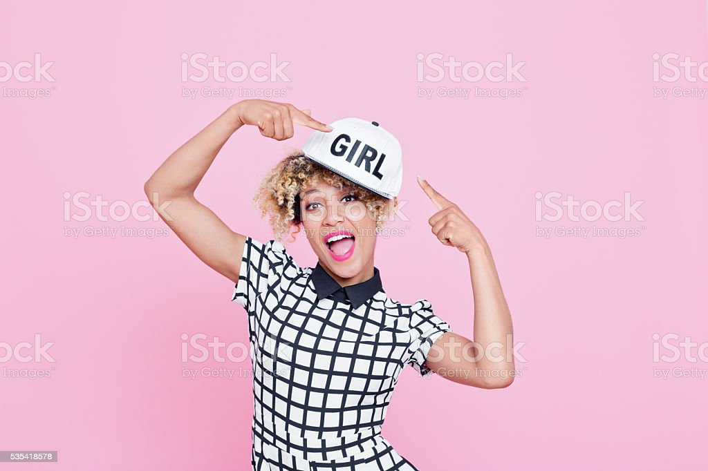 Afro American young woman with white cap Summer portrait of happy, afro american young woman wearing grid check playsuit and white baseball cap, standing with here fingers showing text GIRL at her cap, looking at camera and smiling. Studio shot, pink background. 20-29 Years Stock Photo