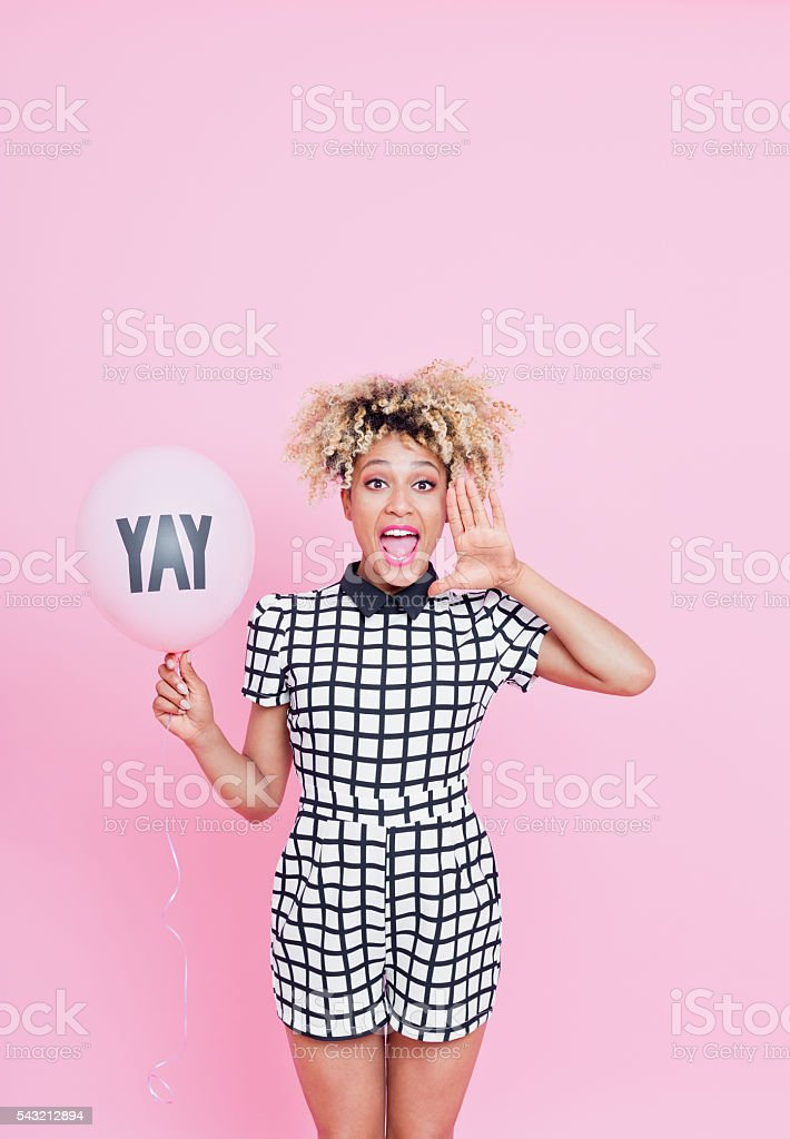 Afro American young woman with YAY balloon shouting stock photo