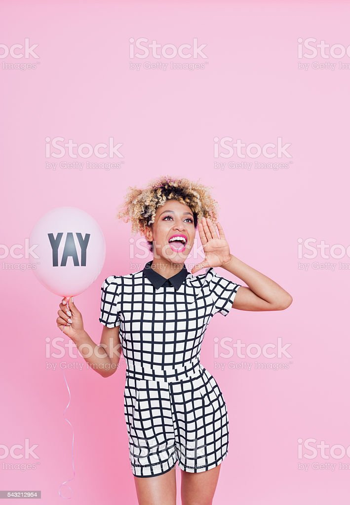 Afro American young woman with YAY balloon shouting Summer portrait of beautiful afro american young woman holding pink ballon, with YAY sign, wearing grid check playsuit, standing against pink background and shouting. Studio shot. 20-29 Years Stock Photo