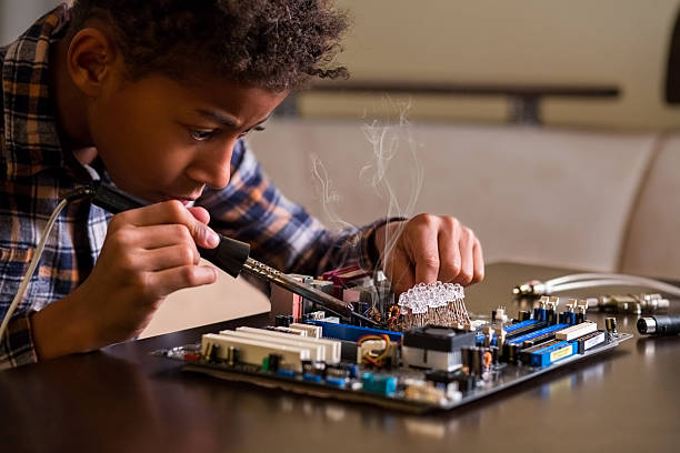 Afro boy fixing motherboard. Afro boy fixing motherboard. Black kid repairs motherboard. Few touches here and there. Everything by the book. soldering iron stock pictures, royalty-free photos & images