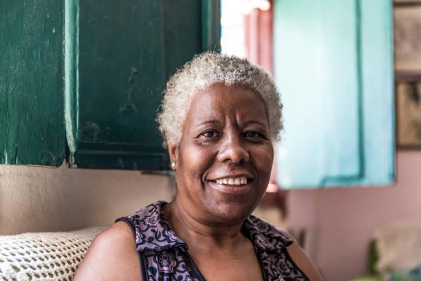 afro brasilianischen frau lächelnd zu hause - altes damenhaar stock-fotos und bilder