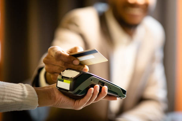 afro businessman giving credit card to barman - contactless payment stock pictures, royalty-free photos & images