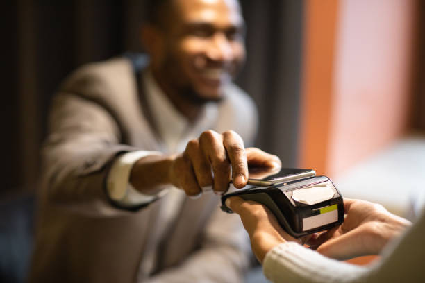 afro businessman paying with his cellphone at bar - paying with card contactless imagens e fotografias de stock