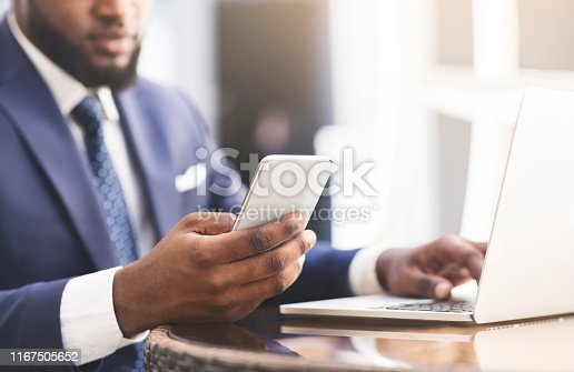 istock Afro Businessman Using Cellphone And Laptop Working In Outdoor Cafe 1167505652