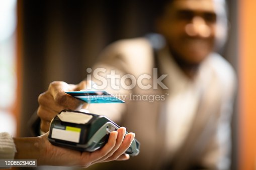 NFC Technology. Smiling afro manager in suit giving credit card to waitress using modern contactless system at the bar