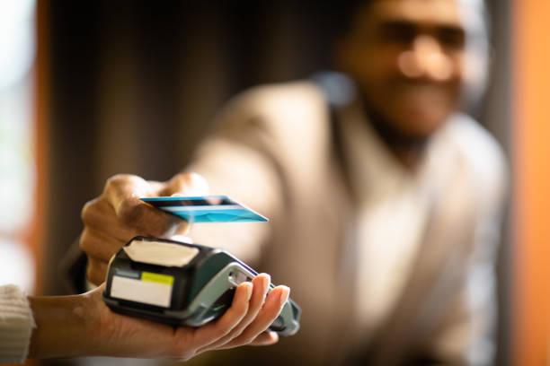 afro businessman using modern contactless system at bar - paying with card contactless imagens e fotografias de stock